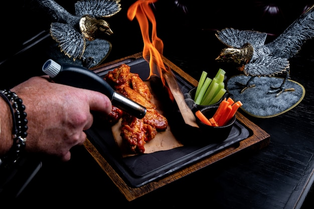Вкусные кусочки куриных крылышек на гриле с огнем пламени. на ресторане черный фон. барбекю и гриль. блюдо ресторана Premium Фотографии