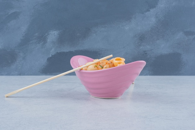 어두운 표면에 마카로니와 젓가락으로 맛있는 핑크 플레이트 무료 사진