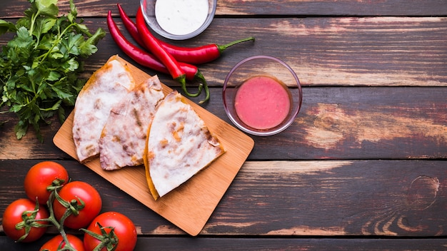 Delicious pita on chopping board near sauces among vegetables and herbs Free Photo