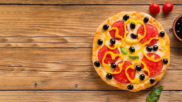 コピースペースを持つ木製のテーブルでおいしいピザ 無料写真