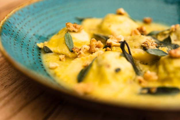 Delicious plate of cooked ravioli pasta on wooden table Free Photo