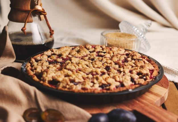 Вкусный сливовый пирог с кофе chemex и ингредиентами с тканью на деревянном столе с тканью Бесплатные Фотографии