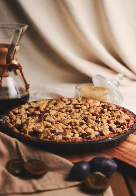 Deliziosa torta di prugne con caffè chemex e ingredienti con tessuto su un tavolo in legno con tessuto Foto Gratuite