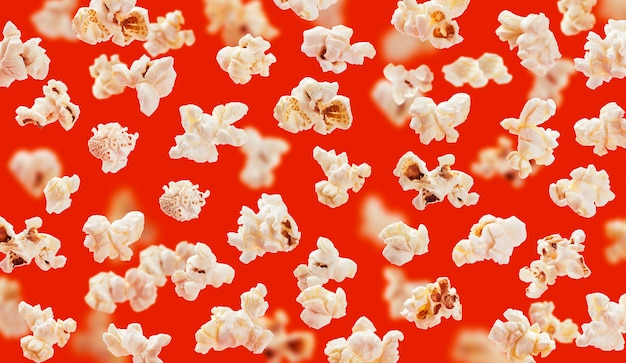 Delicious pop corn grains closeup on red background Premium Photo