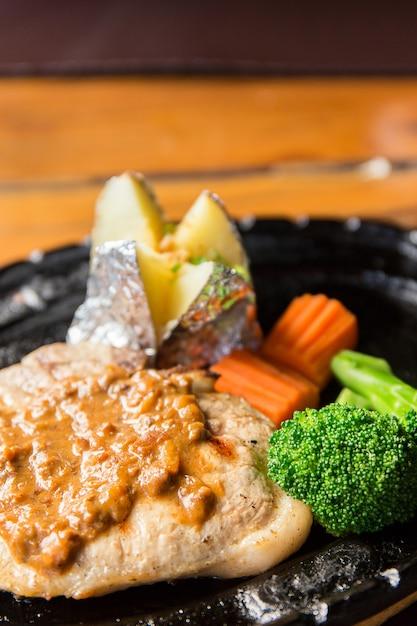 뜨거운 팬에 감자와 야채를 곁들인 맛있는 돼지 고기 스테이크 프리미엄 사진