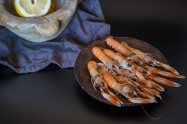 Delicious raw langoustines with a stone mortar full of lemons Premium Photo