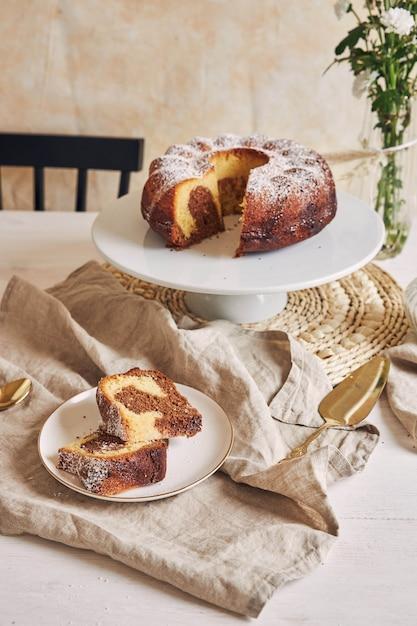 Deliziosa torta ad anello messa su un piatto bianco e un fiore bianco vicino Foto Gratuite