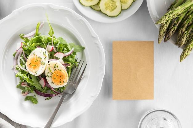Deliziosa insalata su un piatto bianco con scheda vuota Foto Gratuite