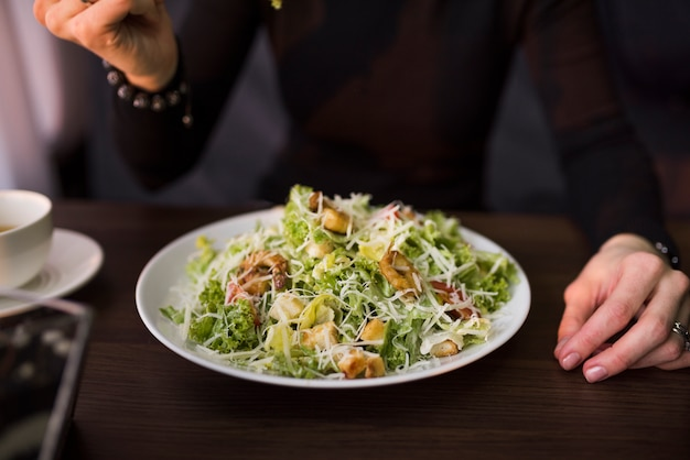 Delicious salad with croutons; shrimp and grated parmesan cheese on table in front of a person Free Photo