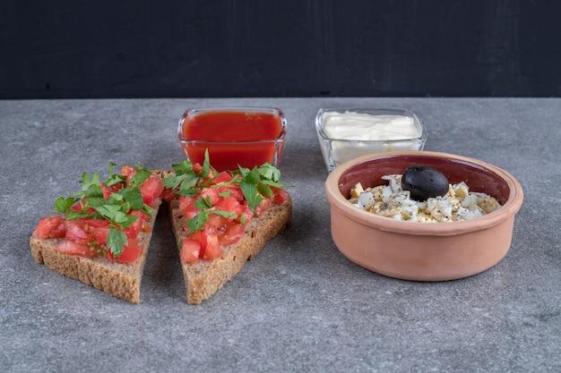 灰色の背景にマヨネーズとケチャップを添えたおいしいサラダ。高品質の写真 無料写真
