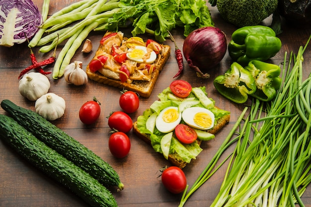 Delicious sandwich with different healthy vegetables on wooden table Free Photo