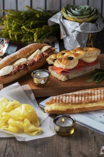 아름답게 장식 된 나무 테이블에 맛있는 샌드위치와 감자 무료 사진