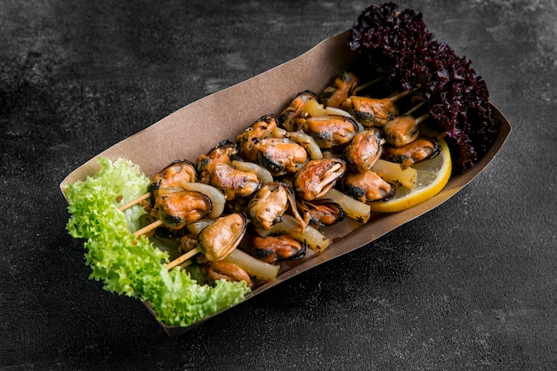 Delicious seafood oysters on skewers in a cardboard Premium Photo