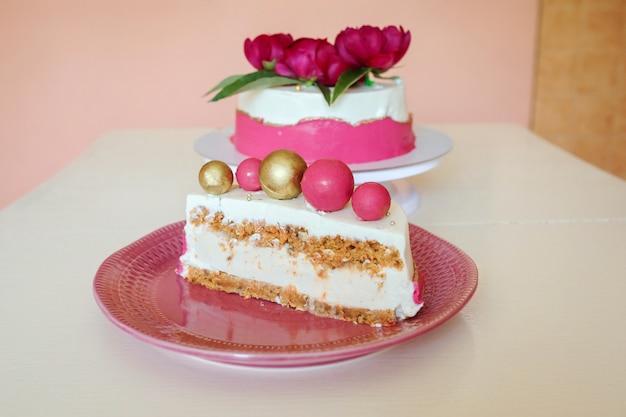 Вкусный кусочек торта, десерт из чизкейка с морковным бисквитом на розовой тарелке перед аппетитным тортом, украшенным цветами пиона. Premium Фотографии