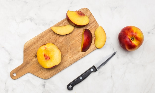 Delicious slices of peach on wooden board Free Photo