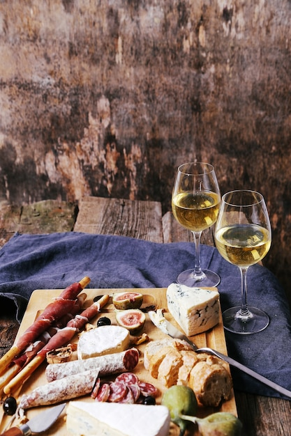 Delicious snacks on wooden board Free Photo
