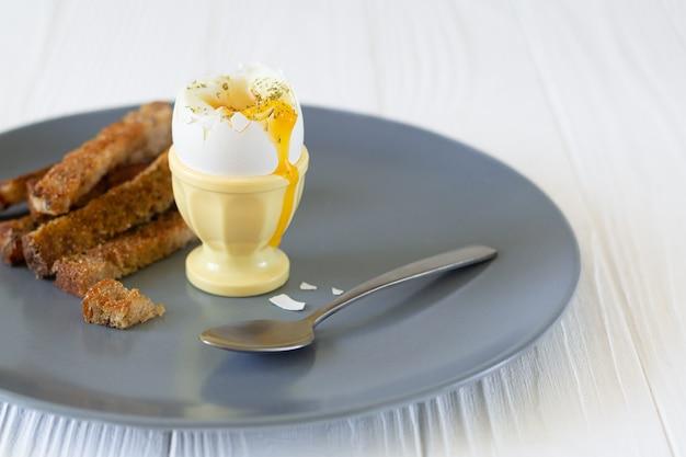 朝食にトーストしたパンが入ったエッグカップに入ったおいしい半熟卵 Premium写真
