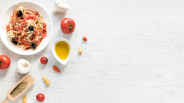 Delicious spaghetti pasta on plate; fresh tomato; bowl of olive oil and herbs on wooden desk Free Photo