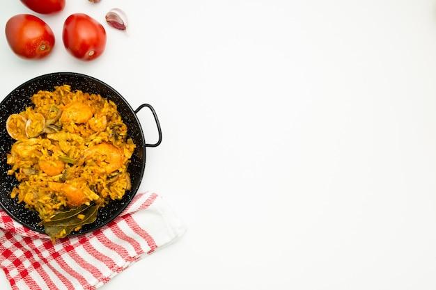Вкусный испанский рис в сковороде паэлья на белом фоне Бесплатные Фотографии