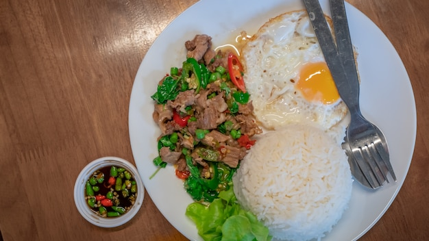 Delicious stir fried spicy meat beef with basil leaves and fried egg Premium Photo