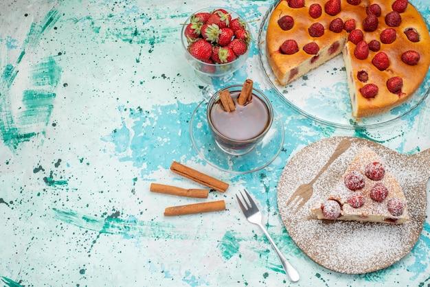 Deliziosa torta di fragole a fette e intera deliziosa torta di zucchero in polvere con tè su un blu brillante, torta ai frutti di bosco dolce da forno Foto Gratuite