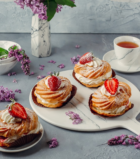 Delicious strawberry cream puff eclairs on marbles board Free Photo
