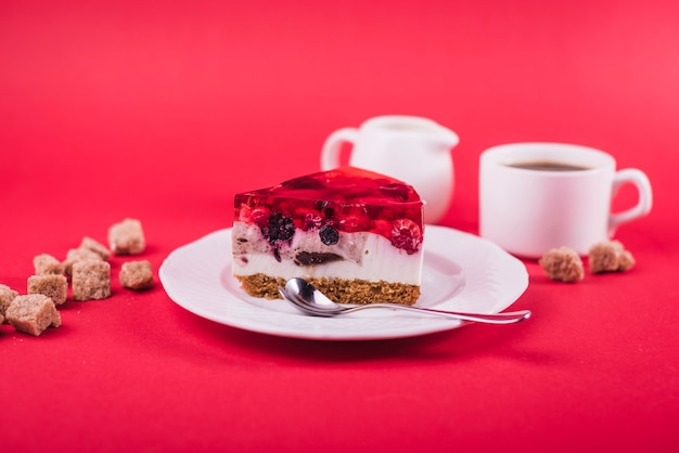 Delicious strawberry jelly and cheese cake on white plate with brown sugar cubes against red backdrop Free Photo