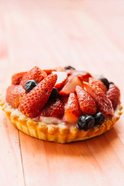 Delicious strawberry tart on wooden backdrop Free Photo