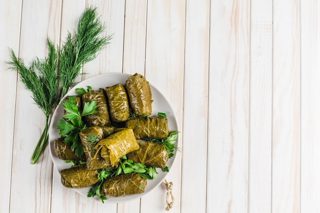 Delicious stuffed grape leaves on a black plate with fresh cilantro and dill Premium Photo