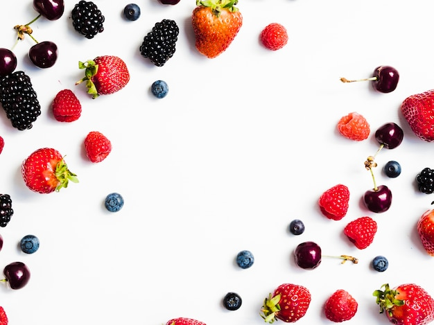 Delicious summer berries on white surface Free Photo