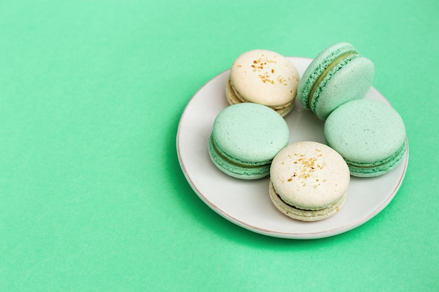 Delicious sweet dessert macaroons in white plate on mint paper background Premium Photo