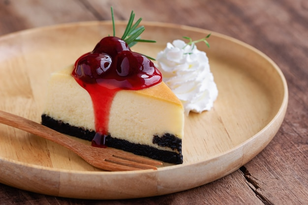 Delicious and sweet strawberry new york cheesecake on wooden plate served Premium Photo