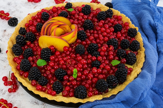 Delicious tart with red currants, peach and blackberries Premium Photo