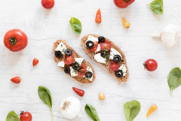 Delicious tasty bruschetta surrounded by healthy ingredient Free Photo