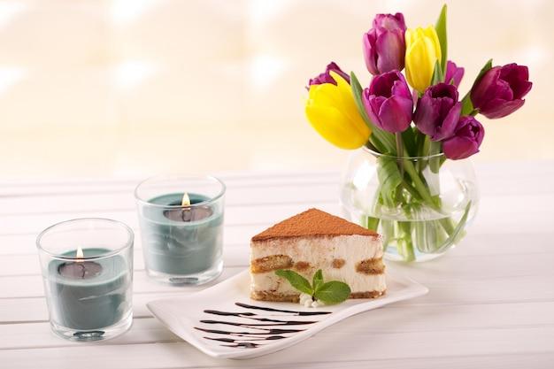 おいしいティラミスケーキとチューリップの花をプレゼントとして Premium写真