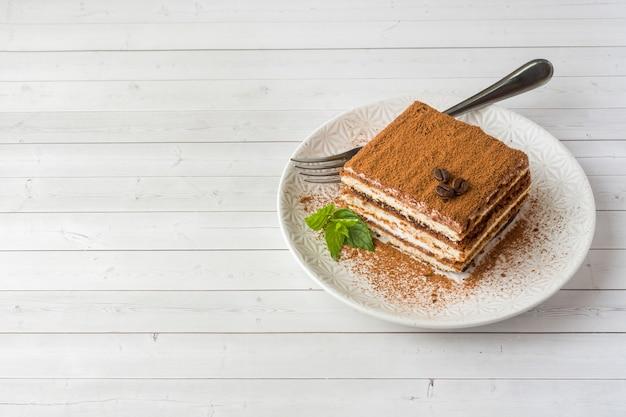Delicious tiramisu cake with coffee beans and fresh mint on a pl Premium Photo