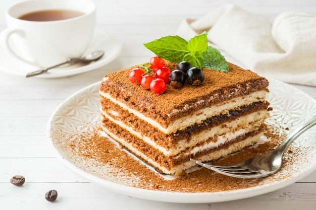 Delicious tiramisu cake with fresh berries and mint on a plate Premium Photo