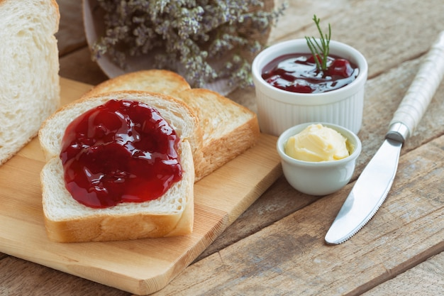 Delicious toast bread served with butter and spread with strawberry jam for breakfast Premium Photo