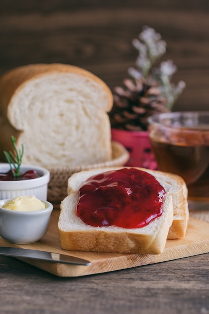 Delicious toast bread with butter and spread with strawberry jam served with hot tea. Premium Photo