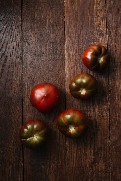 Delicious tomatoes on a wooden background top view Free Photo