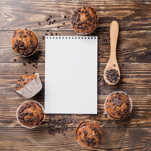 Delicious top view muffins with notepad Free Photo