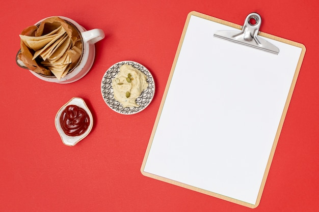 Delicious tortilla with dips next to clipboard Free Photo