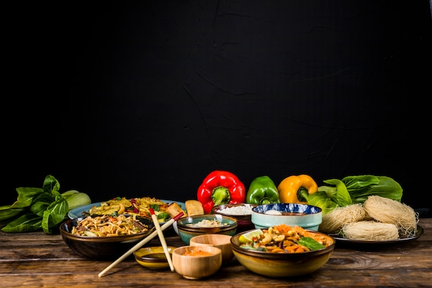 Delicious variety of thai food in different bowls with bokchoy and bell peppers on table against black backdrop Free Photo