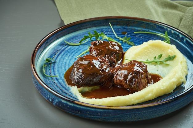 Вкусные телячьи щечки с медовым соусом и пюре гарнир в синюю тарелку на деревянном столе. выборочный фокус Premium Фотографии