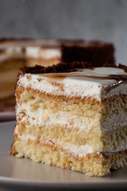 大理石の背景にテーブルの上の皿に白いクリームとおいしいビクトリアスポンジケーキ。ペストリーカフェやカフェメニューの壁紙。垂直。 Premium写真