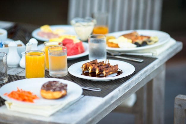 Delicious waffles, cake, coffee and juice served for breakfast at resort restaurant Premium Photo