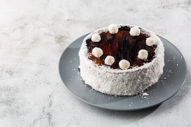 大理石の背景にテーブルの上にココナッツキャンディーとプレートにおいしい全体のチョコレートケーキ。ペストリーカフェやカフェメニューの壁紙。水平。 Premium写真