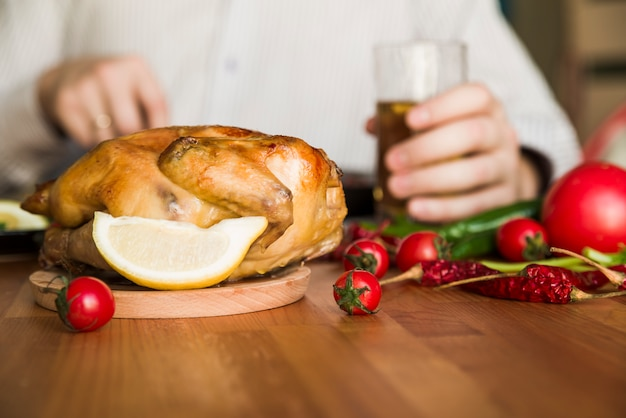 Delicious whole grilled chicken in front of a man holding glass of a beer Free Photo