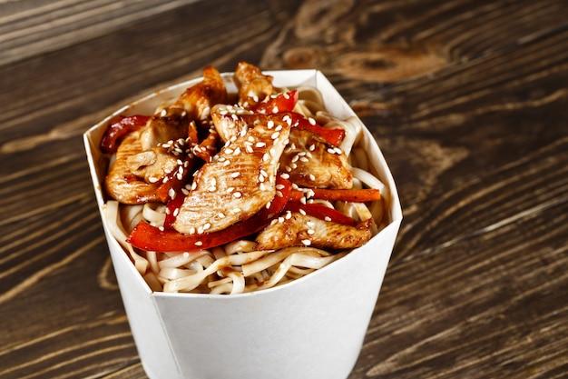 うどんとチキンの木製のテーブルで美味しい中華麺ボックスコンテナーです。中国とアジアのテイクアウトのファーストフード。 Premium写真