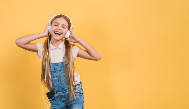 Delight girl enjoying listening the music on headphone against yellow backdrop Free Photo
